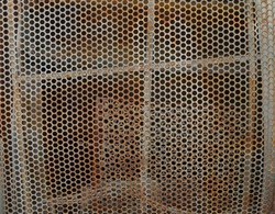 Metal small square wall panel. Style, design texture. perforated holes tiles with tracery. Close-up of interior design material for pattern background.