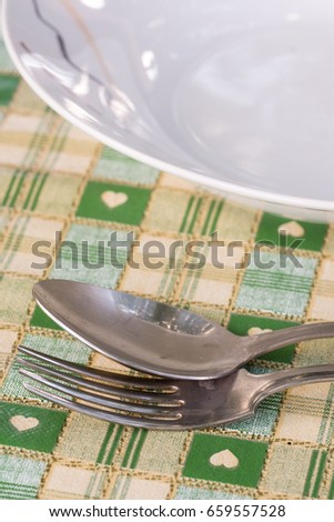 Metal spoon and fork beside plate on the served table. #659557528