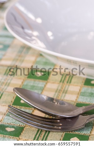 Metal spoon and fork beside plate on the served table. #659557591