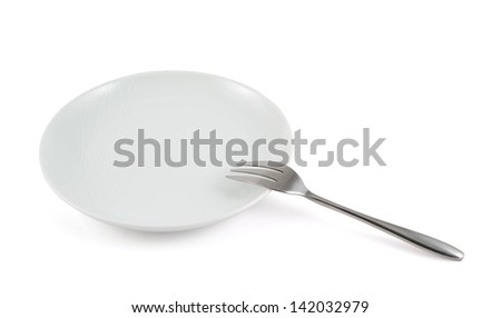 Metal stainless steel fork in a ceramic white plate isolated over white background