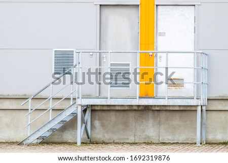 Metal stairs leading to doors. Entrance and exit orange color. Divide. Choice. Small steps. Ventilation. Thinking of reason. Come and go. Stable ground. Light gray aluminum wall.