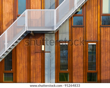 Metal stairs on a modern wooden facade - stock photo
