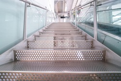 metal stairs step with circle holes next to escalator. Metalic interior midern style