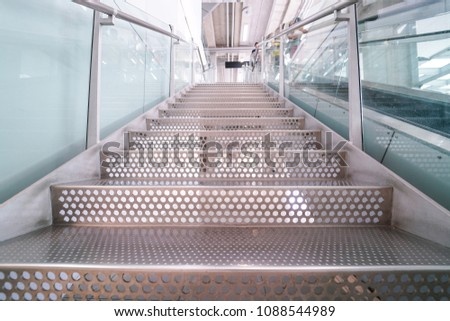 metal stairs step with circle holes next to escalator. Metalic interior midern style #1088544989