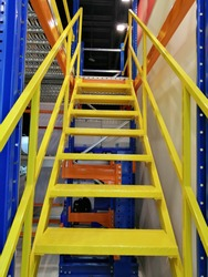 Metal stairs with handrails in logistics/materials handling warehouse.