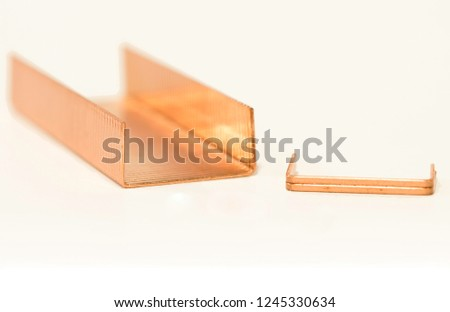 Metal staples of copper for stapler, in insulation with white background. Close up. Macro. selective focus