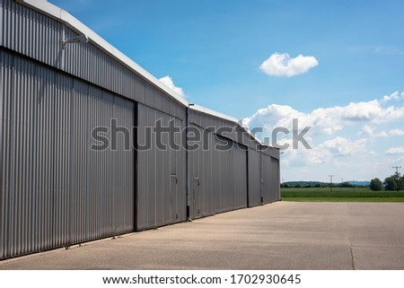 Metal structure hangar from a private airport in Germany. Hangar exterior view on a beautiful summer day. Private airport hangar.