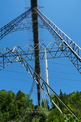 Metal structure of a bridge in upward perspective suspended over an abyss and attached on the banks by complex metal pipes.