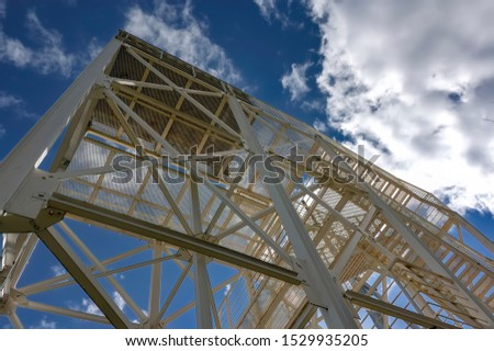 Metal structures against the blue sky and white clouds. #1529935205