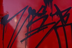 metal surface of the wall painted in red is covered with smeared traces of black paint, vandalism in the urban environment. Background for design. Web banner.