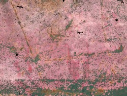 Metal surface painted green and pink, with rust and wear showing through.