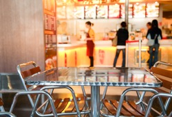 Metal table and chairs at Chinese fastfood cafe in foodcourt with blurred counter menu and tray, focus on furniture - public catering background