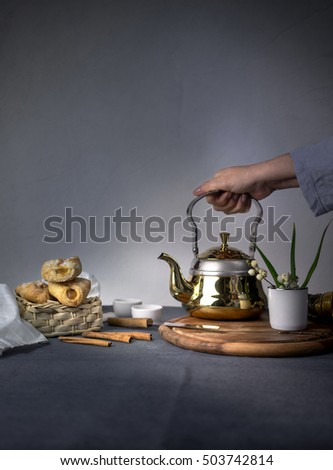 metal tea, cakes and vanilla on dark background #503742814