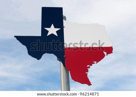 Metal Texas road sign against a cloudy blue sky.
