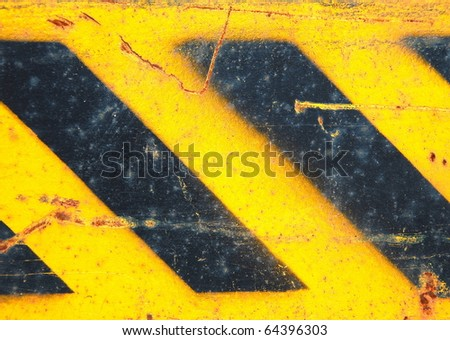 Metal texture with caution sign, scratched surface