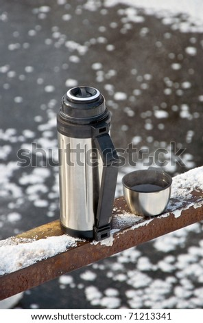 Metal thermos with hot tea drink. Winter.