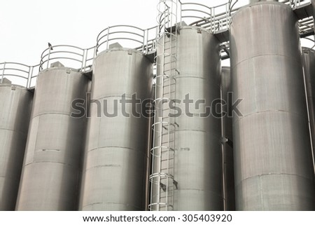 Metal tower silos (for storing bulk materials) of the industrial plant.