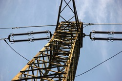 Metal tower supporting high voltage cables. (Photo from below with sky background)