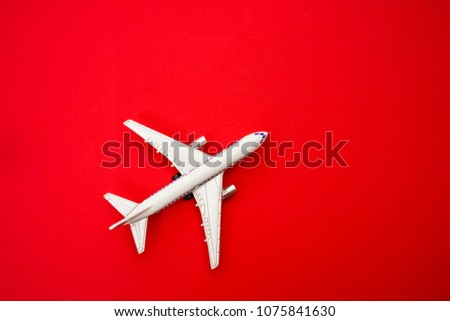Photo of metal toy - airplane stand on red paper background. modern plane isolated  on red backdrop. travel and transportation idea.