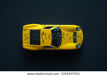Photo of Metal toy sports car of yellow color. View from the top