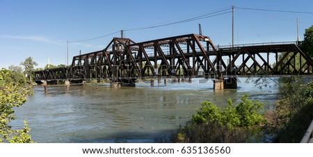 Metal truss swing bridge called I St Bridge across flooded Sacramento River in capital of California #635136560