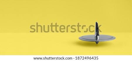 Photo of  Metal Ultimate Gray spinning-top rotation on a yellow Illuminating background, 2021, trendy color, rotation, color of the year
