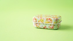 Metal vintage jewelry box with Floral print. Tin box container on green background