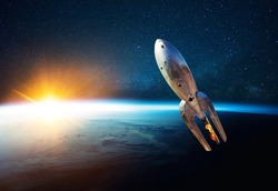 Metal vintage rocket with fire takes off into open starry space near the planet earth with sunset. Retro spacecraft lift off and flies on a background of the starry sky, planet and sunlight
