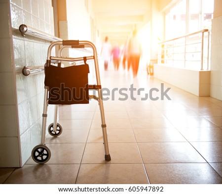 Metal walker parked in hospital hallway.