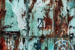 Metal wall of an abandoned hangar in Russia. Rusty grunge background with faded turquoise paint, bullet marks and number 203. Beautiful abstract texture for design or urban exploration website.