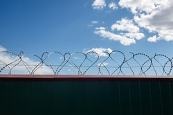 Metal wall with barbed wire against the blue sky background. Fence with barbwire for protection, space for text