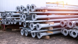 Metal warehouse indoor of lighting poles. Storage of metal galvanized faceted pipes with flange.