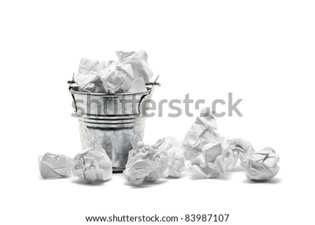 Metal waste basket filled with crumpled paper - waste or frustration concept