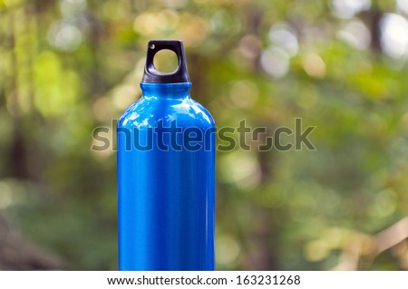 Metal water bottle in green forest over blurred background, hiking and sport equipment