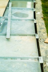metal water drain or ditch in a construction site. Gutters drain grate, drain cover. garden drains - sewer cover.  Water go down to the drain under the metal.