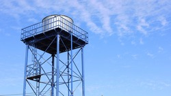 Metal water tank on the tower. Structure and storage tanks in the water supply system on a blue sky background with a copy area. Selective focus