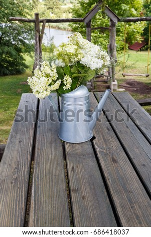 metal watering can with field flowers bouquet on the table #686418037