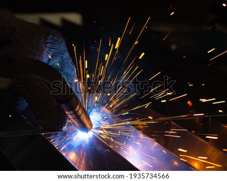 Metal welder works with a steel welder in a factory with protective equipment. Manufacture of metal structures and repair and construction services according to the concept of manual labor. Photo stock ©