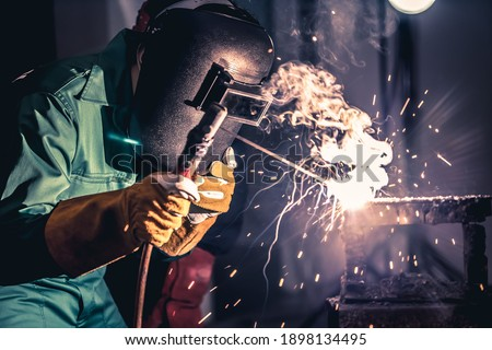Metal welding steel works using electric arc welding machine to weld steel at factory. Metalwork manufacturing and construction maintenance service by manual skill labor concept. Photo stock ©