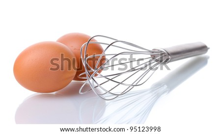 Metal whisk for whipping eggs and brown eggs isolated on white