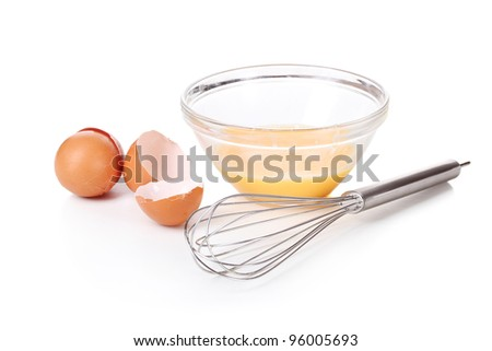 Metal whisk for whipping eggs and eggs in bowl isolated on white
