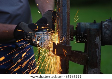 metal worker sawing iron with sparks spreading
