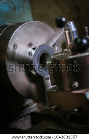 Metal worker shaping metal on lathe #1043801557