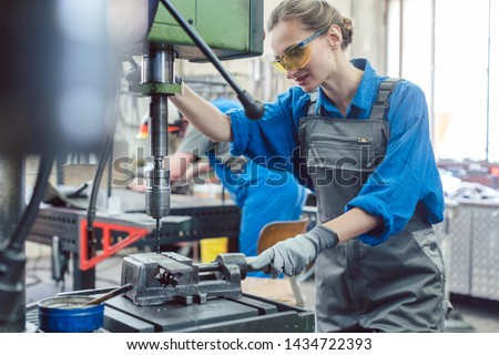 Metal worker woman operating drilling machine concentrating on her job #1434722393
