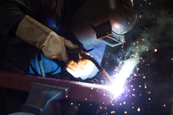 Metal workers use manual labor, Skilled welder, Factory workers making OT, The welder is welding the steel in the factory, Welding fumes, The welder stands to weld the iron in the dark