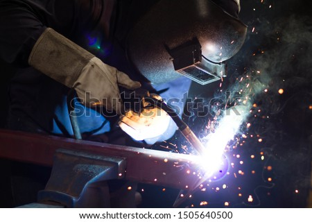 Metal workers use manual labor, Skilled welder, Factory workers making OT, The welder is welding the steel in the factory, Welding fumes, The welder stands to weld the iron in the dark  #1505640500