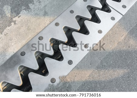 Metal zigzag pattern edge of drainage channel on concrete floor. #791736016