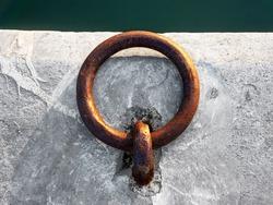 metallic and rusty mooring ring on dock
