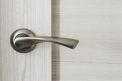 Metallic chrome door knob on wooden door as a background