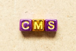 Metallic color alphabet letter block in word CMS (Abbreviation of Content management system) on wood background
